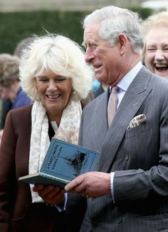 Prince Charles, Prince of Wales and Camilla, Duchess of Cornwall look at a copy of 'A Fleet in Being' by Rudyard Kipling they were presented with as they visit Bateman's, the East Sussex home of the author, on March 19, 2014 in Burwash, United Kingdom.