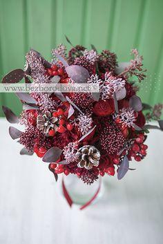 Зимний свадебный букет из красных роз и ранункулюсов с ягодами гиперикума и шишками