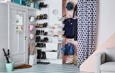 An organised hallway by the door filled with shoes and coats and things for a family of three  or