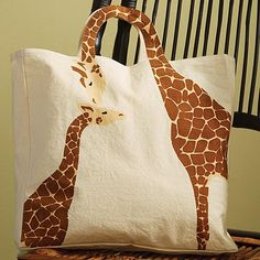 A tote with surprise design details: a magnetic snap closure and handles that follow the graceful curve of the mother giraffe's neck. 15'w x 14'h (not including handle) x 3'd. Natural cotton canvas, printed on one side.