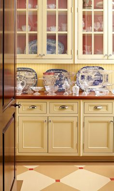 """In the butler's pantry, the homeowner's collection of glassware and blue-and-white porcelain is set off against Farrow & Ball's """"Blazer"""" red - Traditional Home®"""