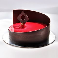 Cake with bananas and chocolate. Decor dark chocolate and red mirror glaze.