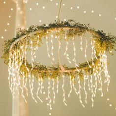 "Having a rustic wedding or sprucing up an outdoor space? Grab a $1 Dollar Tree hula hoop and create a ""chandelier"" by painting it white and wrapping it with hanging lights and greenery. Then, suspend it with rope from the ceiling of your venue or even from a tree branch."