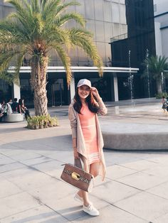 Spring outfit streetstyle: Blush / coral dress, semi-long cardigan, white sneakers / keds, and a pretty baseball cap.