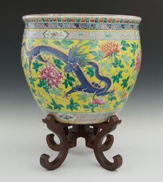 "A Large Chinese Porcelain Famille Rose Jardiniere on Wood Stand, Late Qing Dynasty. Of bulbous shape with flat rim. Hand enameled in polychrome and decorated with two Imperial Dragons among blossoming flowers on yellow background; hand enameled with koi fish among sea grass inside. Unmarked. 15-3/4""T x 18-1/2""D at the widest point."