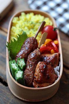 Ethnic-style bento box featuring saffron rice, shish kebabs, chicken tikka, & bell pepper parmesan saute