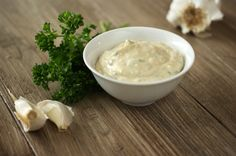 best Aioli sauce in a bowl, garlic and parsley on the side