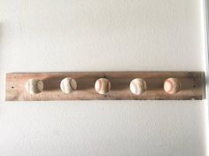 This is the best way to hang up all those baseball hats that your kids use on a daily basis.  We use a plank of wood measuring approximately 36 inches and added 5 baseballs to it.  You are welcome to supply the baseballs from your own special occasions, such as game balls or home run