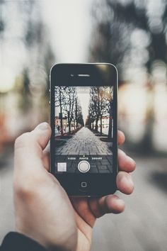 This image shows how much social media takes over our lives, because this image was taken with a camera, but the subject is an iphone taking a picture outside.