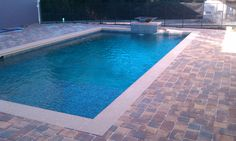 Rustic pavers for this pool.  Don't forget the water feature.  Ahhhh.  Relaxing!