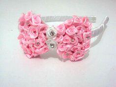 Tiara flexível forrada em cetim branco e laço bordado em rosas e strass. R$ 19,70