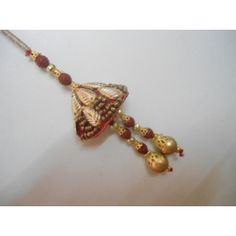 """Surprise your bhabi in India by sending this blue colored Lumba Rakhi through orlygifts.com.Red satin base creates a cone shape which is the main part of this lumba. The base is intricately decked with zari, golden leaves and glitters. The """"Lathkans"""" that are hanging from the conical base come with red swead n golden beads. A pack of roli chawal also come along free."""