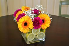 Created this inexpensive floral arrangement for Aunt's 60th Birthday party using Golden Gerbera Daisies, Magenta Carnations, Baby's Breath, Lemons and Square Vase