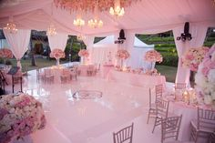 lavish wedding reception under marquee tent, uplighting and massive flower bouquets