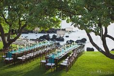 Teal table runners on dark wooden farm tables illuminated by chandeliers hanging from the trees at Kukahiko Estate for a luxury outdoor wedding dining experience by Bliss