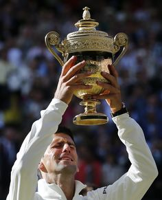 Novak Djokovic of Serbia reacts as he holds trophy after defeating Switzerland's Roger Federer in the men's singles final match at the All England Lawn Tennis Championships in Wimbledon (AP)