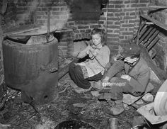A German girl knits, while her brother repairs a pair of shoes he has found in the streets of Berlin after the end of WWII and the Allied occupation of the city.