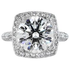 4.15ct Round Brilliant Diamond Solitaire Ring  Platinum custom Solitaire Ring consisting of one Round Brilliant Diamond weighing 4.15cts. with an ideal cut and a GIA Color and Clarity grade of K+ / SI2+ the center stone is surrounded by approximately 1.25cts. pave set full cut Diamonds.