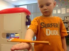 A young student has several pencils balancing on the back of his outstretched ha