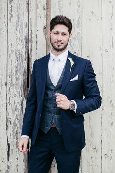 GROOM Groom wearing navy blue suit with tartan waist coat for wedding.  Wedding Editorial Photography