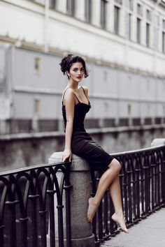 Sexy black dress, great hairstyle with most of the hair up, but one strand of hair hanging down.