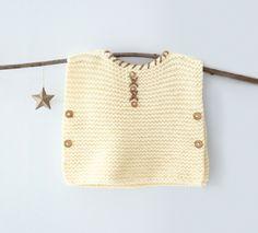 Accessoire indispensable dans le dressing de bébé ! On adore les petits boutons en finition. Tricoté en 'Laine RAPIDO', coloris Craie et Beige.Modèle N°3 du catalogue N°129 : Automne/Hiver 2015, Layette Facile.