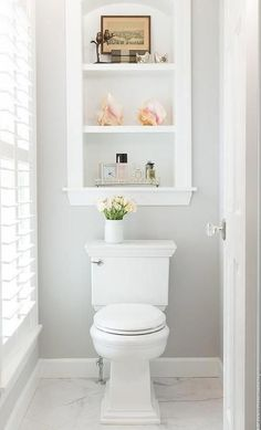 Custom inset shelves over a toilet in a transitional white and gray bathroom. #bathroomwindow
