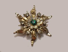 "1940 Copper Pinwheel Brooch with 14 clear 1 green rhinestone 1.75""  SOLD"