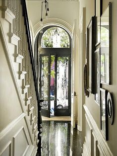 Black doors frame an arched doorway ~ black rail on white spindles of the stairway
