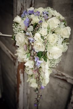 Wedding bouquet: White roses, baby's breath, hydrangea and ceropegia. Blue flowers from hydrangea and agapanthus.