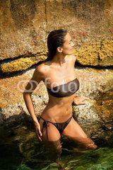 belle femme debout dans de l'eau transparente sur un rocher