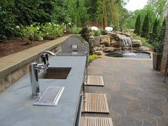A custom made outdoor kitchen with an inground spa in the background. The patio consists of Belgard Mega Arbel pavers.