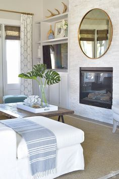 Decorating with Mirrors. Family Room with round mirror above fireplace.