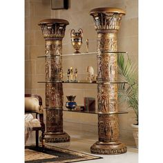 Ancient Egyptian Columns of Luxor Shelves. Rising like the famed Egyptian columns for which it is named, our seven-foot-tall work of furniture art is intricately carved and crowned with lotus leaf capitols. Cast in resin and dramatically hand-painted wit