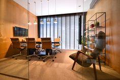 Sala de reuniões do Escritório E3 Arquitetura, com paredes revestidas com carvalho, mesa de madeira ebanizada e estante em ferro