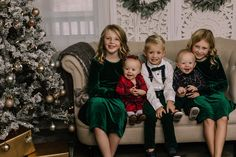 holiday mini session photo shoot christmas dresses bow ties suspenders plaid velvet siblings cousins neutral greenery garland tree lights screen sofa couch hugging babies twins