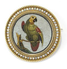 A MICROMOSAIC BROOCH BY CASTELLANI  The circular micromosaic panel depicting a green and red parrot perched on a branch to the white background and blue and white enamel border, one small tile deficient, 5 cm wide  Stamped CC for Castellani