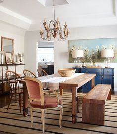 """understated furnishings no-frills farm table, mismatched seating—a distressed bench, three Windsors, and a velvet Louis XV armchair—and painted sideboard) and accessories with a hint of patina (like Shana's ever-so-slightly tarnished silver). """"I don't like feeling stuck in one era or style,"""" Shana says. The striped rug adds a graphic pop that orients everything squarely in the 21st century."""