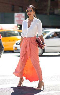 Mulher posa para foto no meio da rua com saia coral de amarração, camisa branca aberta e segurando uma clutch