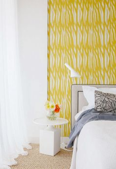 Yellow patterned wallpaper in bedroom with white and gray bedding