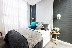 Soft grey colour palette accented with timber creates an inviting bedroom space