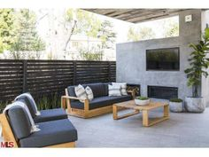 A modern and trendy outdoor living area with an outdoor fireplace and flat screen television. Los Angeles, CA Coldwell Banker Residential Brokerage $4,250,000