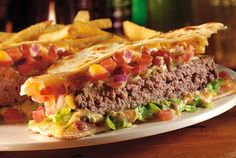 burger_Quesadilla Hambúrguer de 200g coberto com queijo Jack-cheddar, bacon, tomate, cebola roxa, alface e jalapeños. Servido entre duas tortillas de trigo, temperado com pico de gallo e molho Mexi Ranch.