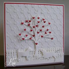 What a sweet touch to have all white with only tiny red hearts. Would look great even if it was simpler...no fence or dogs, just tree and hearts with the embossed background.