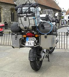 Rear view of motorcycle fitted with panniers, top box, and extra soft luggage