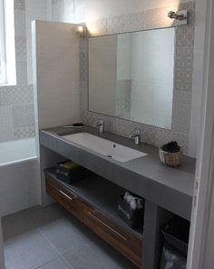 Un meuble en béton ciré gris Baho, pris entre 2 murs. 2 tiroirs en teck lamellé vernis pour un maximum de rangement.