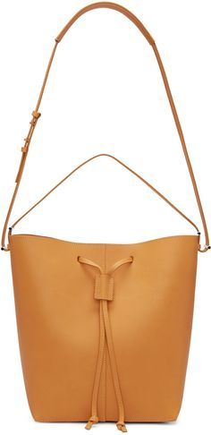 Structured vegetable-tanned leather bucket bag in tan. Single adjustable shoulder strap with post-stud fastening. Leather drawstring closure at bag throat. Zippered pocket in grey suede at interior. Silver-tone hardware. Tonal stitching. Approx. 12