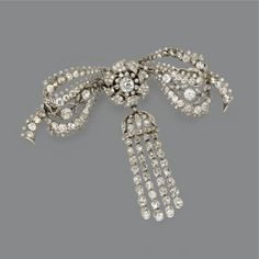 DIAMOND BOW BROOCH, CIRCA 1910 The lacework bow supporting a central tassel with chain fringes, set throughout with numerous old-mine, single-cut and rose-cut diamonds weighing approximately 10.25 carats, mounted in platinum.
