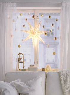 Bring a little twinkle to overcast skies with the help of some golden tree ornaments. If you use an extendable shower curtain rod inside the window frame, you can hang IKEA ornaments so they don't get in the way of the curtains. Attach the decorations using fishing line, so they appear to float. And they are really easy to put up and take down