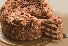 Rococo Chocolate Gateaux: Chocolate fresh cream layered with chunks of chocolate chip cookies and whirls of chocolate ganache between three layers of a moist chocolate torte, covered with fine chocolate shavings.